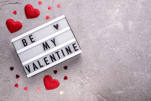 Soyez ma boîte à lumière valentine avec des coeurs rouges sur fond de ciment avec espace de copie