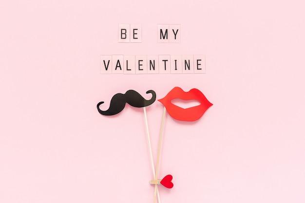 Soyez ma saint-valentin et un couple de moustaches en papier, des accessoires pour les lèvres sur fond rose.