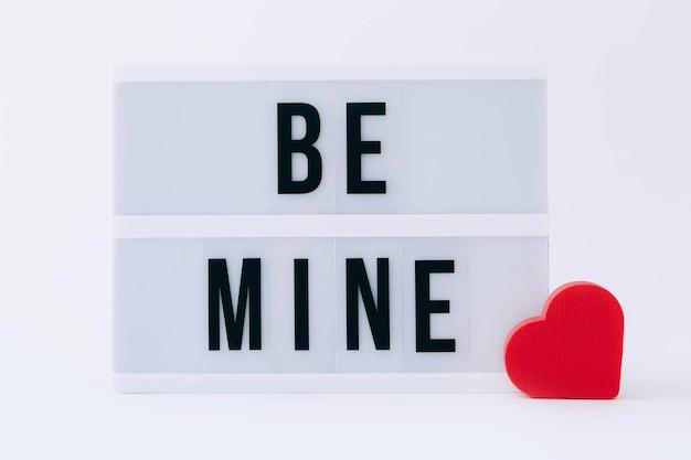 Soyez le mien message lightbox avec éponge coeur rouge sur une table lumineuse, gros plan