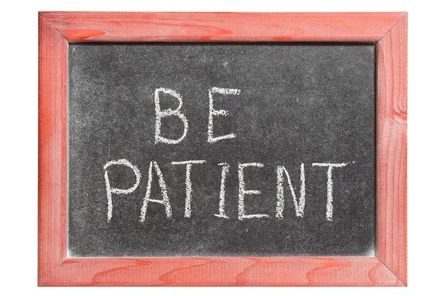 Soyez patient phrase manuscrite sur tableau noir vintage isolé