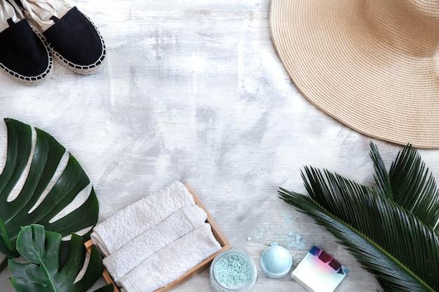 Spa. articles de soins du corps sur fond blanc avec des feuilles tropicales. accessoires d'été. espace pour le texte.
