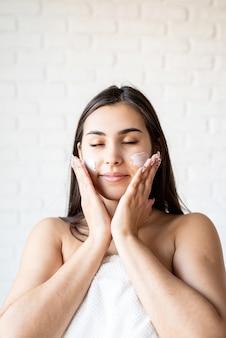 Spa et beauté. heureuse belle femme caucasienne portant des peignoirs de bain appliquant une crème pour le visage sur son visage