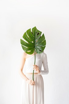 Spa et beauté. soins personnels et soins de la peau. heureuse belle femme dans des vêtements confortables tenant une feuille de monstera verte