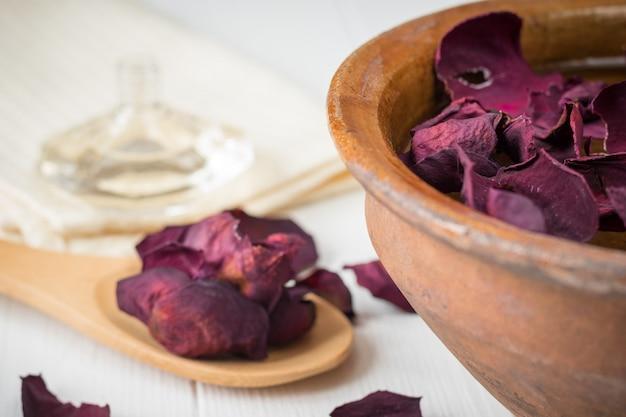 Spa avec de beaux pétales de rose et un bol en argile.