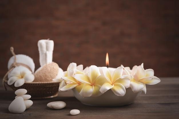 Spa bien-être et traitement aux huiles essentielles, pierre zen, serviettes, bougie, boule de massage du cœur et fleurs de frangipanier sur table en bois avec mur de briques