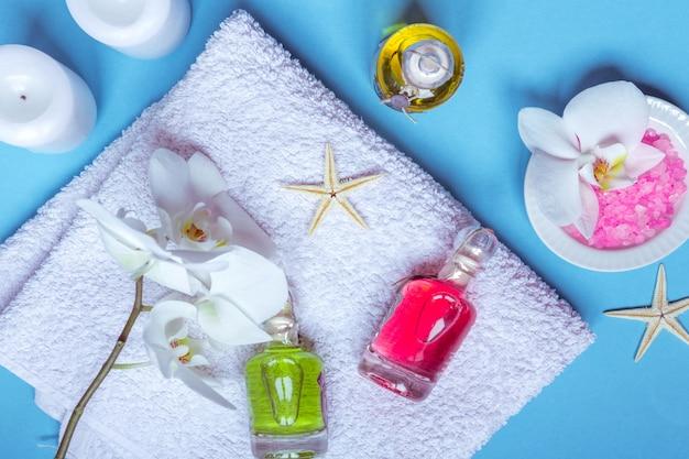Spa cadre nature morte avec fleur d'orchidée, bougie, savon et serviettes sur fond bleu