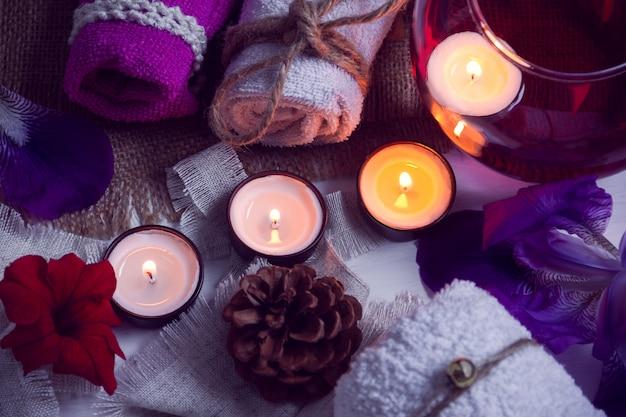 Spa composé de serviettes, bougies, fleurs, cônes et eau d'aromathérapie dans un bol en verre