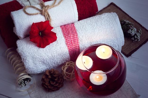 Spa composé de serviettes, bougies, fleurs et eau d'aromathérapie