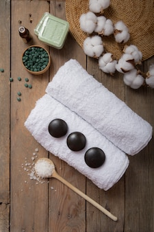 Spa, cosmétiques de beauté et concept de traitement de soins du corps avec espace de copie. composition créative à plat vue de dessus avec accessoires de bain spiruline verte, pierres, huile, sel de mer, savon