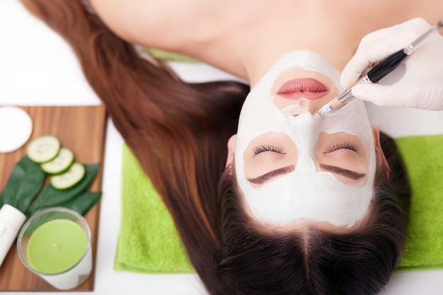 Spa femme appliquant le masque nettoyant pour le visage. soins de beauté. masque à l'argile