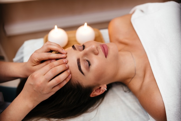 Spa. femme appréciant le massage facial anti-âge.