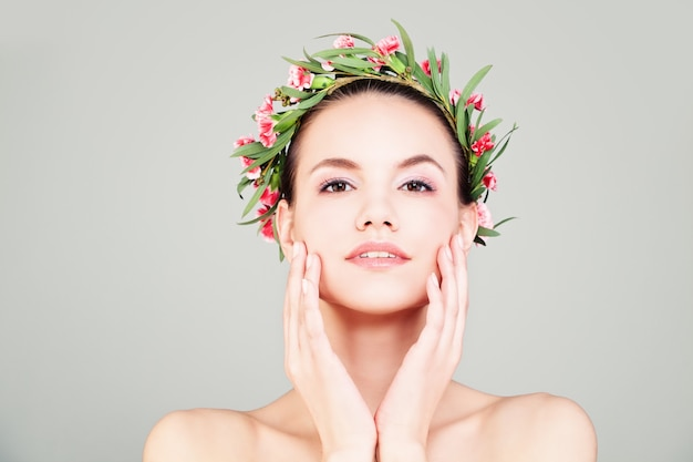 Spa femme avec couronne de fleurs d'été. beauté naturelle. le modèle la touche face à sa main