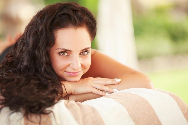 Spa. femme recevant un traitement spa lastone en plein air.