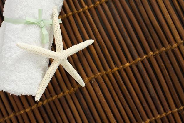 Spa ou fond de bien-être avec serviette blanche sur tapis de bambou