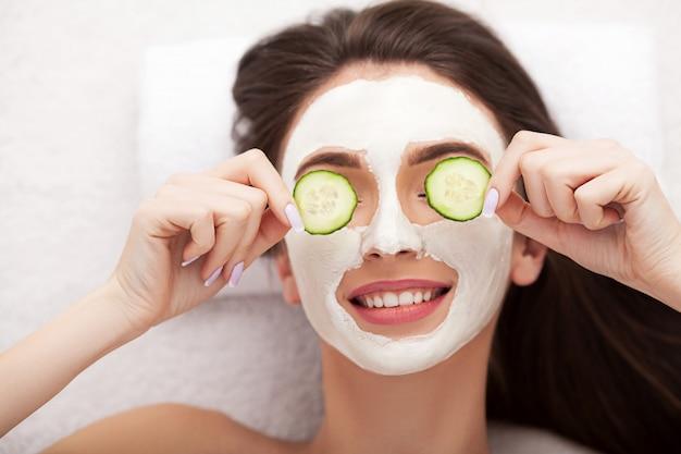 Spa. jolie femme drôle avec un masque d'argile sur son visage