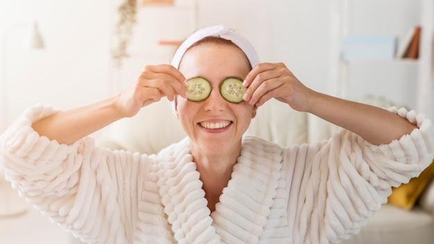 Spa à la maison femme cachant ses yeux avec des tranches de concombre