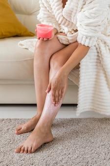 Spa à la maison femme en peignoir à l'aide de crème