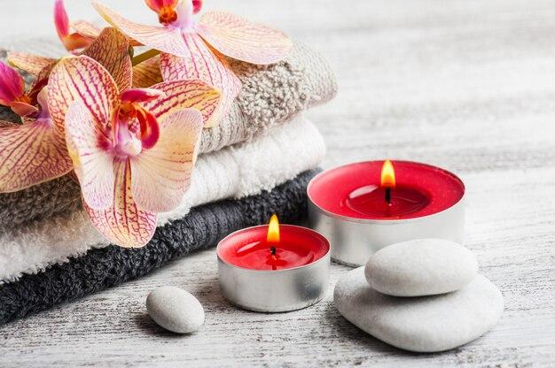 Spa nature morte avec bougies allumées et orchidée orange rouge