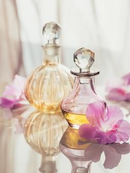 Spa nature morte avec des bouteilles de parfum et d'huiles aromatiques entourées de fleurs, sur une surface claire