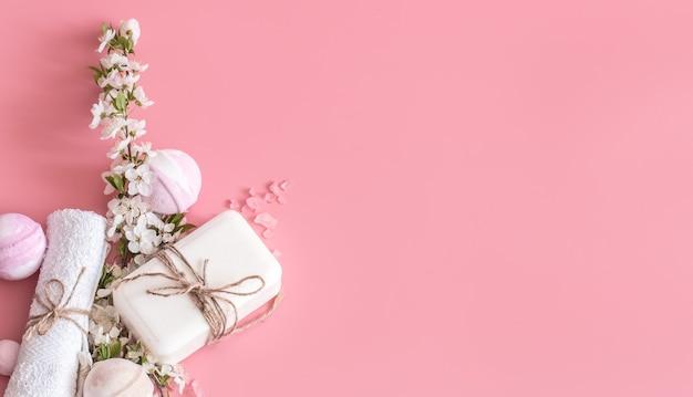 Spa nature morte sur mur rose avec des fleurs de printemps