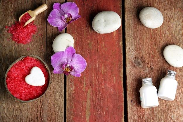 Spa nature morte pour la saint-valentin dans des couleurs rouges et blanches avec des fleurs d'orchidées et des pierres de massage