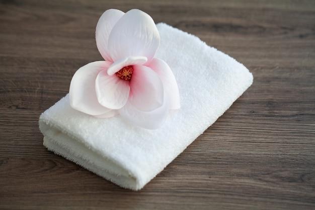 Spa orchidée avec des serviettes douces sur une table en bois