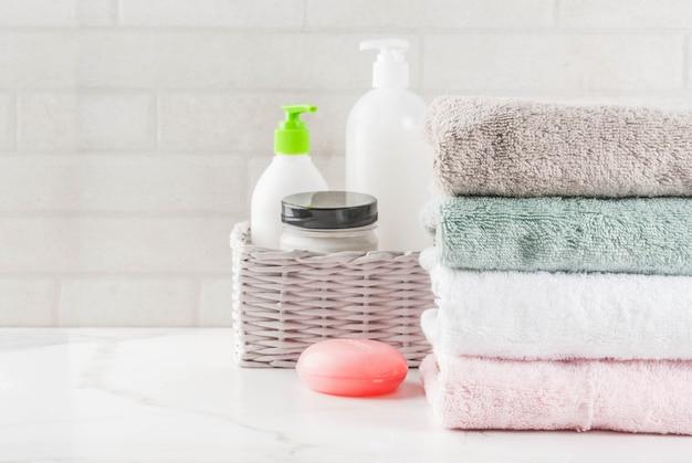 Spa relax et concept de bain, sel de mer, savon, avec des cosmétiques et des serviettes dans la salle de bain vue de dessus de la surface blanche