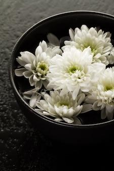 Spa relax concept. belle fleurs de spa blanc dans le bol dans l'eau. fond sombre.