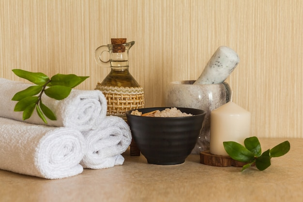 Spa, serviette beauté et bien-être, huile de massage cosmétique, feuille fraîche, sel de mer aux coquillages et bougie