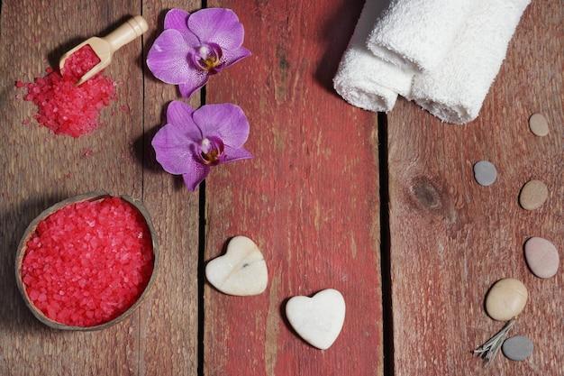 Spa situé sur des planches rouges avec des coeurs en pierre pour le massage, du sel de bain, des serviettes et des fleurs d'orchidées roses
