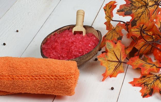 Spa situé sur une table en bois blanche et près des feuilles d'érable d'automne orange