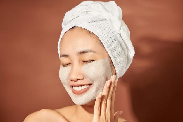 Spa woman appliquant un masque d'argile pour le visage. soins de beauté.