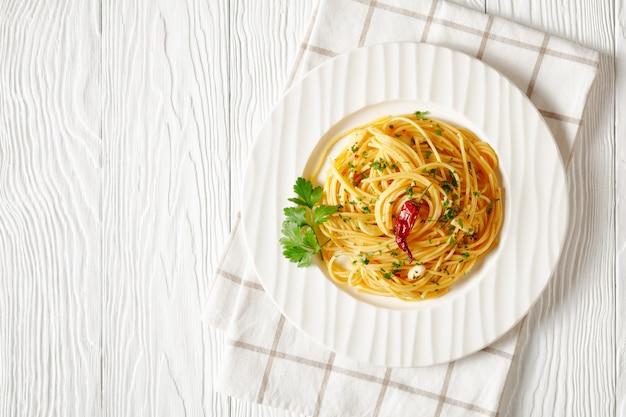 Spaghetti alla colatura di alici, spaghetti à la sauce aux anchois, piment, ail et persil sur une plaque blanche sur une table en bois blanc, vue horizontale d'en haut, mise à plat, espace libre