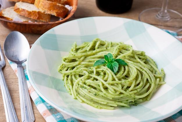Spaghetti au pesto sur une assiette blanche et verte avec du pain et un verre de vin