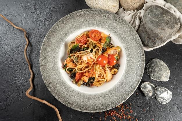 Spaghetti au saumon et légumes. un plat principal chaud composé de pâtes, poisson de mer, tomates, câpres, olives et olives