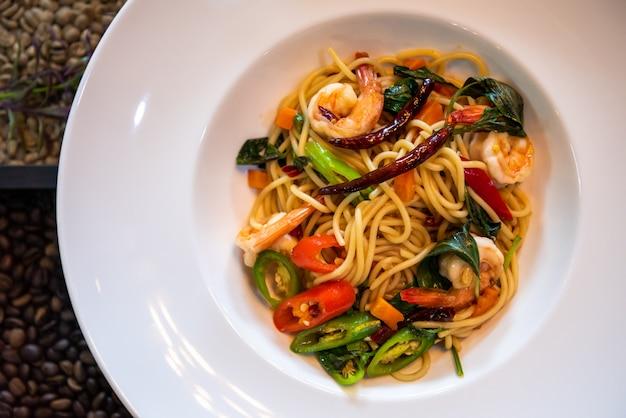 Spaghetti aux crevettes épicées dans un plat blanc fermé