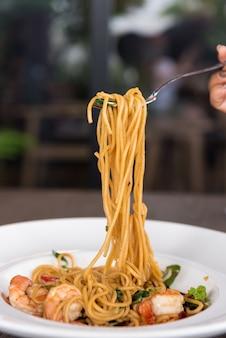 Spaghetti aux crevettes épicées dans un plat blanc.
