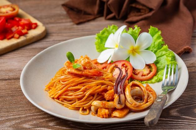 Spaghetti aux fruits de mer avec sauce tomate décoré avec de beaux ingrédients.