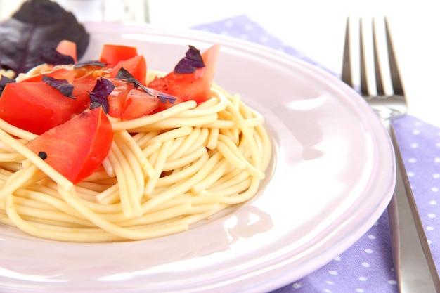 Spaghetti aux tomates et feuilles de basilic sur serviette sur bois