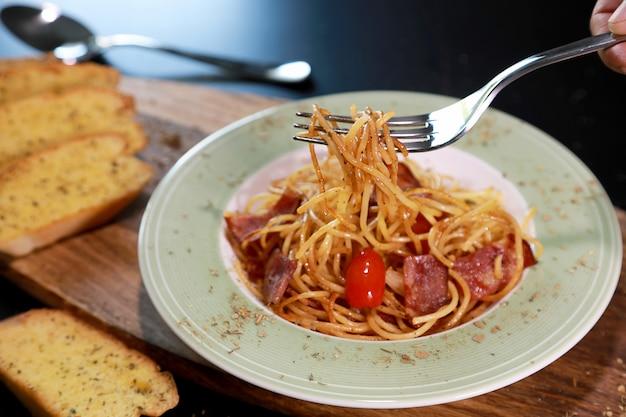 Spaghetti bacon avec fourchette à la main et tomate dans la plaque de couleur verte et blanche et pain à l'ail.
