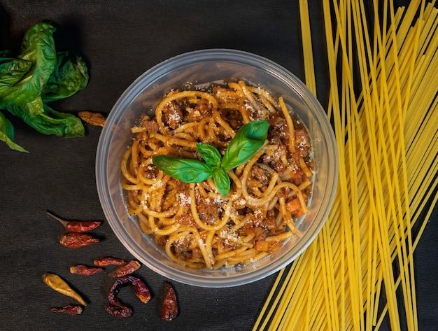 Spaghetti bolognaise servi sur fond noir foncé avec piment et basilic, vue d'angle supérieur