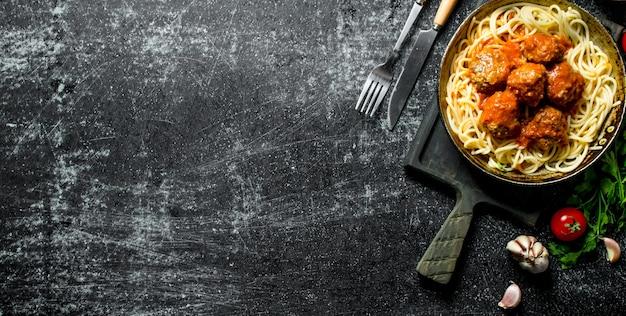 Spaghetti et boulettes de viande dans une vieille casserole avec de l'ail et des tomates sur table rustique