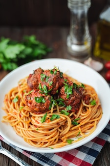 Spaghetti et boulettes de viande à la sauce tomate dans un plat blanc sur une planche en bois rustique