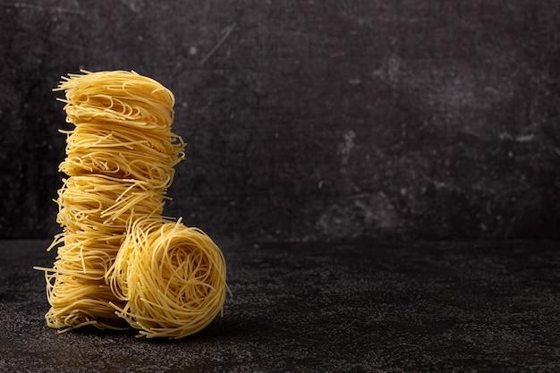 Spaghetti capellini sur un fond structurel sombre avec un espace pour copier. spaghetti empilé dans une tour