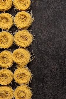 Spaghetti capellini sur un fond structurel sombre avec un espace pour copier. vue de dessus. espace de copie