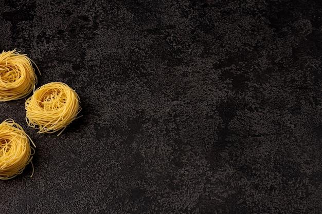 Spaghetti capellini sur fond structurel sombre avec espace pour copier