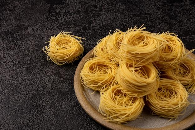 Spaghetti capellini sur une plaque en céramique sur un fond structurel sombre avec un espace pour copier des spaghettis