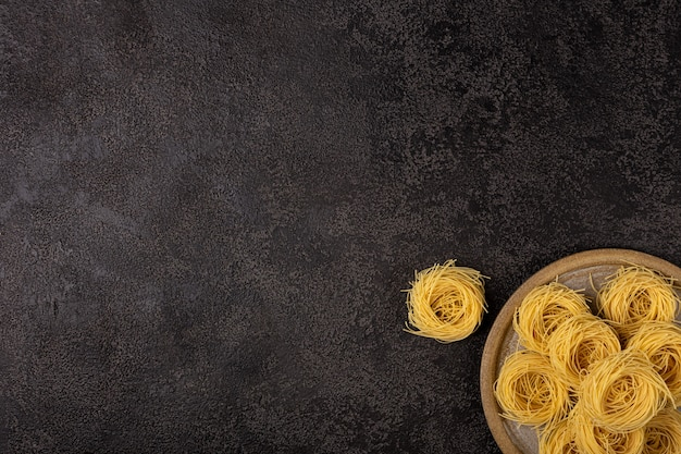 Spaghetti capellini sur une plaque en céramique sur un fond structurel sombre avec un espace pour copier