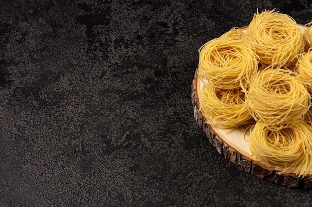 Spaghetti capellini sur un plateau en bois sur un fond structurel sombre avec un espace pour copier