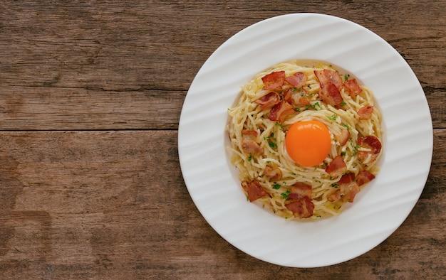 Spaghetti carbonara au bacon, fromage, jaune d'oeuf et persil haché sur une table en bois en vue de dessus